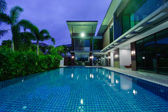 Casa moderna con la piscina alla notte Fotografie Stock Libere da Diritti
