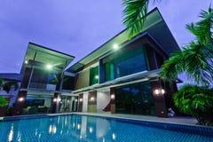 Casa moderna con la piscina en la noche Fotografía de archivo libre de regalías
