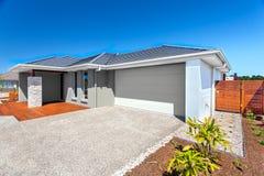 Casa moderna con un área del garaje y del patio trasero y el cielo azul Foto de archivo