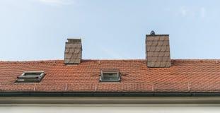 A casa moderna da ripa com chaminé e o telhado iluminam-se Fotografia de Stock Royalty Free