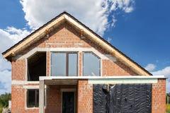 Casa moderna del ladrillo bajo construcción contra el cielo azul imagenes de archivo