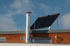 Casa moderna della famiglia con i comitati solari sul tetto Immagini Stock