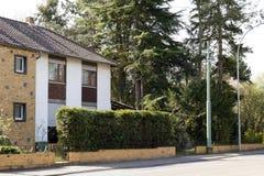 Casa moderna della famiglia sulla via rurale circondata con gli alberi verdi fotografia stock