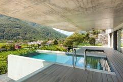 Casa moderna en el cemento, piscina Foto de archivo libre de regalías
