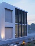 Casa moderna exterior con la iluminación al aire libre en el crepúsculo Imagenes de archivo