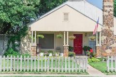 Casa modesta orgulhosamente que indica a bandeira americana e que pendura a flor Foto de Stock Royalty Free