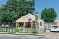 Casa modesta orgulhosamente que indica a bandeira americana e que pendura a flor Fotografia de Stock