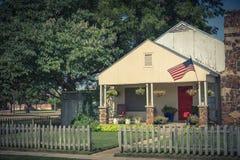 Casa modesta orgulhosamente que indica a bandeira americana e que pendura a flor Foto de Stock