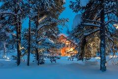 Casa morna na floresta nevado do inverno da noite imagens de stock