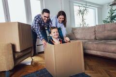 Casa movente da família com caixas ao redor, e tendo o divertimento fotografia de stock