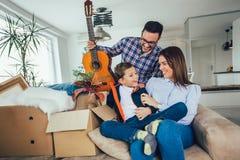 Casa movente da família com caixas ao redor, e tendo o divertimento imagens de stock