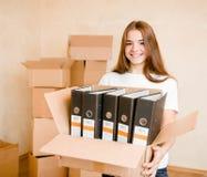 Casa movente da jovem mulher à casa nova que guarda caixas de cartão Fotos de Stock Royalty Free