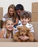 Casa movente do rapaz pequeno e da menina com pais Foto de Stock