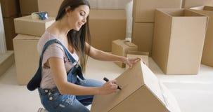 Casa movente e embalagem da mulher atrativa Fotografia de Stock