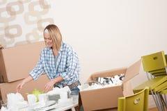 Casa movente: Mulher feliz que desembala pratos imagem de stock