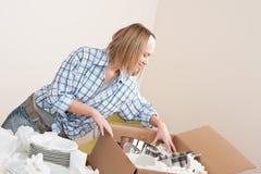 Casa movente: Mulher feliz que desembala pratos imagens de stock