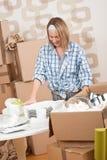 Casa movente: Mulher feliz que desembala pratos imagem de stock royalty free