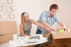 Casa movente: Pares novos que desembalam pratos fotografia de stock royalty free