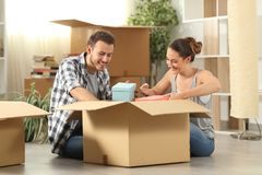 Casa movente unboxing dos pertences dos pares felizes foto de stock royalty free