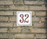 Casa número 32 treinta y dos números marrones en un const blanco de la placa Fotos de archivo libres de regalías