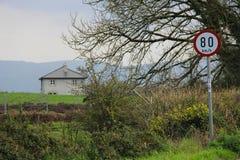 Casa na borda da estrada na Irlanda com sinal da velocidade 80 km/h Imagens de Stock Royalty Free