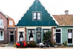 Casa na Holanda dos shans do zaanse, na rua Hugge, na bicicleta holandesa e na motocicleta estacionadas perto de uma construção h fotos de stock