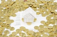A casa na pilha de moedas de ouro tem moedas de ouro ao redor Imagens de Stock