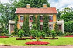 Casa nacional del viejo vintage sueco con las flores delante de ella Imagen de archivo