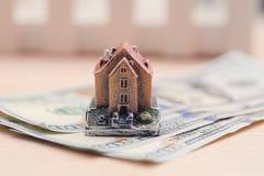Casa nas denominações do dinheiro, o conceito de comprar um propert Fotos de Stock Royalty Free