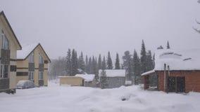 Casa nas madeiras nas montanhas no tempo do inverno Natureza no inverno durante a queda de neve pesada Panorama da paisagem lento vídeos de arquivo