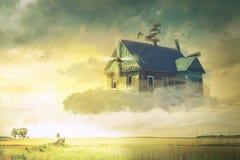 A casa nas nuvens que pairam acima da terra imagens de stock