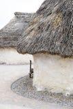 A casa Neolítico da exposição em Stonehenge, Salisbúria, Wiltshire, Inglaterra com avelã cobriu com sapê o telhado e o feno da pa Fotografia de Stock Royalty Free