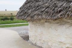 A casa Neolítico da exposição em Stonehenge, Salisbúria, Wiltshire, Inglaterra com avelã cobriu com sapê o telhado e o feno da pa Imagem de Stock