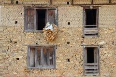 Casa Nepali vieja tradicional con el maíz dejado hacia fuera para secarse fotografía de archivo
