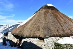 Casa nevado antiga do palloza feita com pedra e palha Piornedo, Ancares, Galiza, Espanha fotografia de stock royalty free