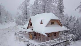 Casa nevosa di legno in terreno boscoso video d archivio