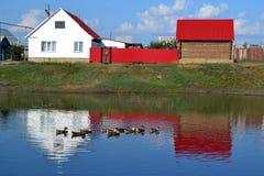 Casa no banco de uma lagoa imagens de stock