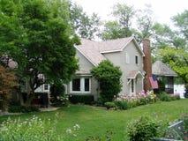 Casa no lago com bandeira e flores 1. Imagens de Stock Royalty Free