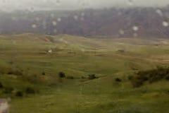 Casa no monte nas montanhas Vista através do vidro molhado Foto de Stock Royalty Free