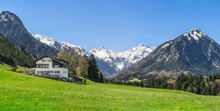 Casa no prado da flor e montanhas cobertos de neve no fundo imagens de stock