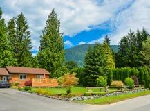 Casa norteamericana de la familia en zona rural con el jardín agradable ajardinado fotografía de archivo