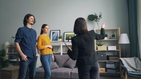 Casa nova da exibição do corretor de imóveis aos pares que falam quando compradores que olham em torno do sorriso