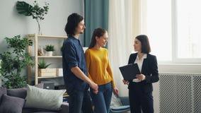 Casa nova da exibição do mediador imobiliário aos compradores que falam discutindo o contrato