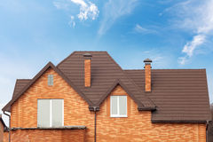 Casa nova do tijolo com chaminé modular, a telha de telhado revestida de pedra do metal, as janelas plásticas e a calha da chuva fotografia de stock