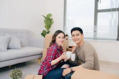 Casa nova movente dos pares Povos casados felizes para comprar o apartamento novo imagens de stock