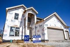 A casa nova terminou parcialmente, sob a construção na subdivisão residencial do alojamento com para venda assina dentro a jarda imagens de stock