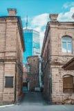 Casa obsoleta do tijolo em um fundo de um arranha-céus Imagem de Stock Royalty Free