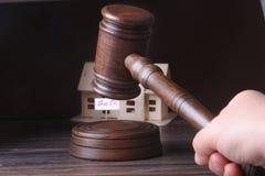 Casa para a venda, o martelo do leilão, o símbolo da autoridade e a casa diminuta Conceito da sala do tribunal fotos de stock royalty free