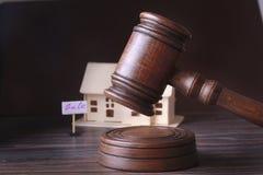 Casa para a venda, o martelo do leilão, o símbolo da autoridade e a casa diminuta Conceito da sala do tribunal fotografia de stock royalty free