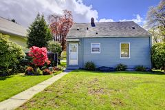 Casa pequena azul com paisagem da mola do quintal. Imagens de Stock